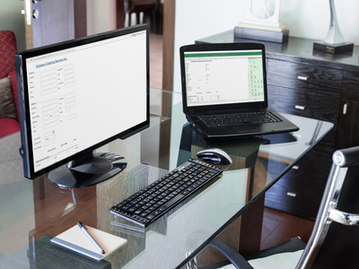 Photo of a laptop with a form developed in Excel and a desktop with the same form as a web page in Google Chrome